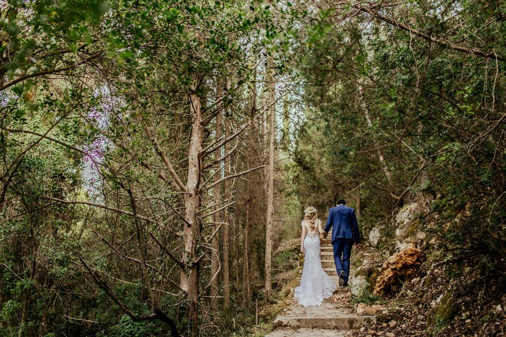 Bride and groom walking up stairs through a forest