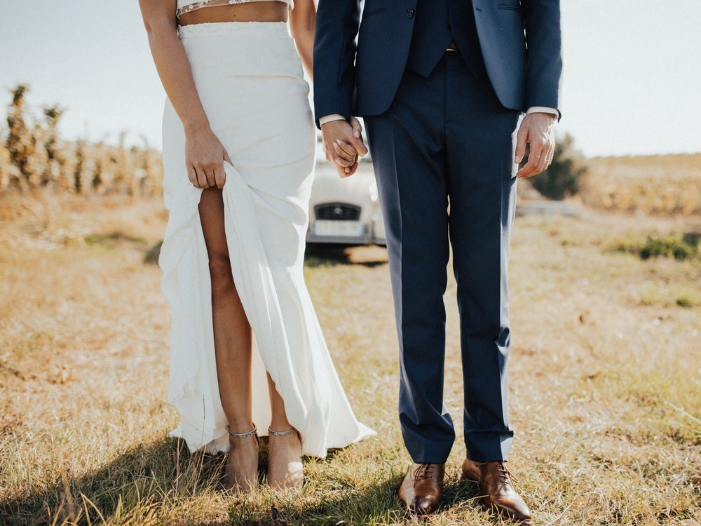 Bottom half of couple standing off-road on grass