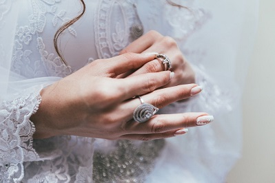 Description: Texas bride touches her wedding ring on finger in front of white lace wedding dress