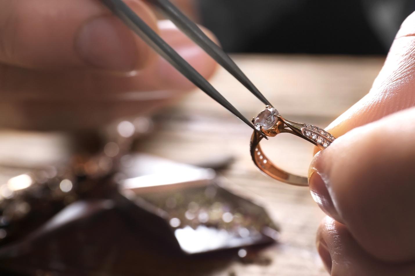 jeweler removing diamond from mount