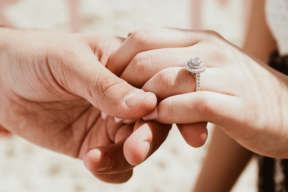 Man holding woman's hand with diamond ring